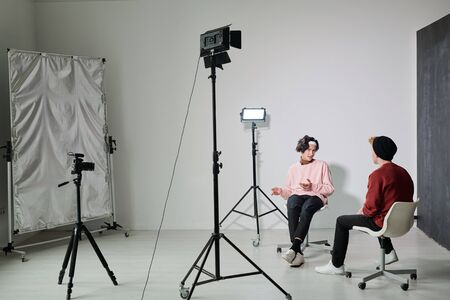 One of two young male vloggers explaining something to his friend in studio Stock fotó