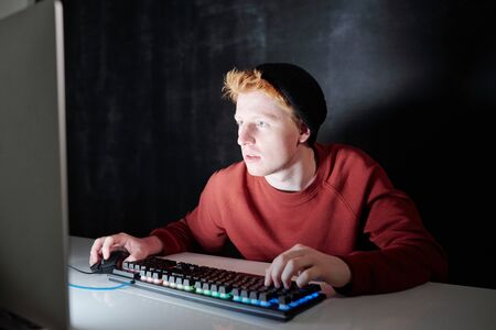 Guy in sweatshirt and black beanie pressing keys of keypad and clicking mouse