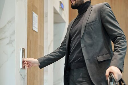 Young elegant businessman pushing button on the wall while standing by door and waiting for elevator in hotel