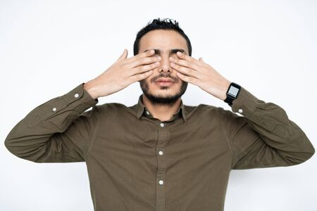 Young tired man in shirt covering his eyes by hands at break between work