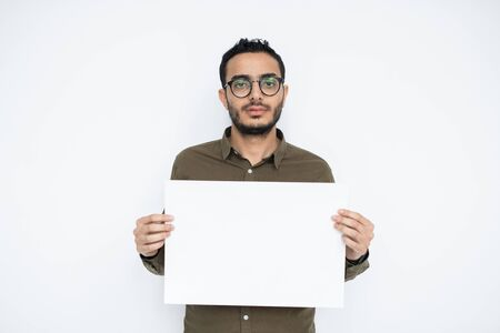 Young businessman with blank face holding empty poster for advertisement