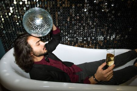 Tired man with disco ball by head and flute of champagne relaxing in bathtub