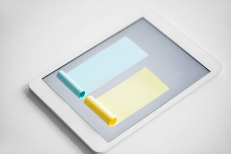 Chart made up of blue and smaller yellow notepapers stuck on screen of digital tablet against white background