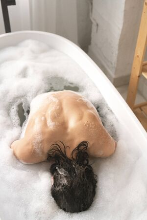 Young naked man keeping his face in water while sitting in bath with foam