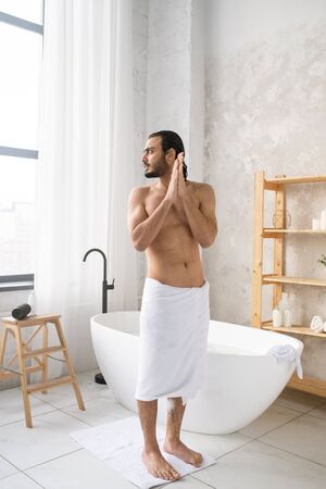 Young clean muscular man with towel on hips standing on the floor of bathroom
