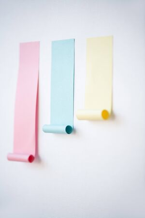 Chart made up of pink and smaller blue and yellow notepapers stuck on whiteboard in isolation