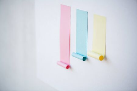 Colorful chart made up of blank pink and smaller blue and yellow sticky papers stuck on whiteboard or wall Imagens