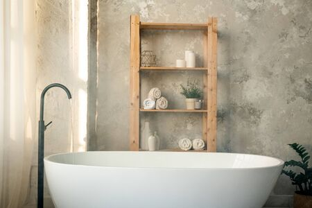 Large porcelain white bathtub and wooden shelves against grey wall in bathroom