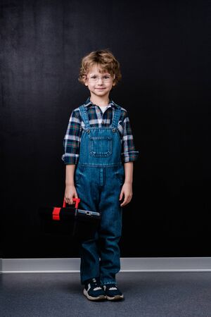 Happy little boy in denim overalls and eyeglasses holding toolbox