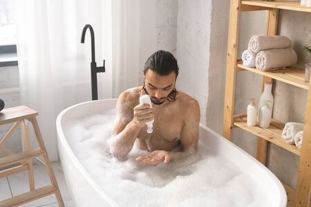 Wet young shirtless man using shower gel while having bath with foam