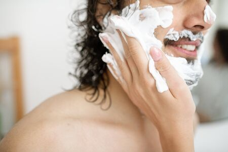 Hand of young woman applying shaving foam on face of happy bearded man