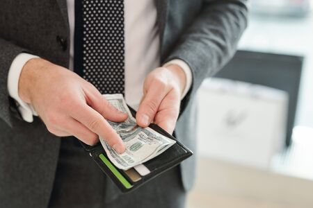 Hands of rich young elegant businessman in suit holding wallet and dollar banknotes while going to pay for something