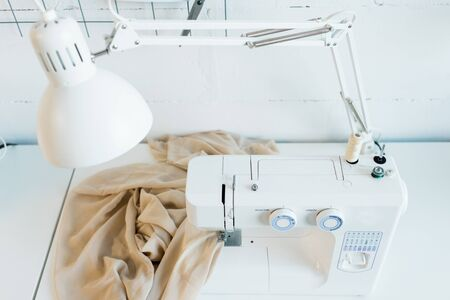 Above view of workplace with electric sewing machine, desk lamp and fabric