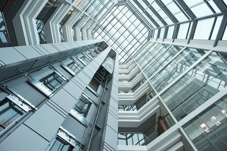 Part of interior of contemporary tall office building with moving elevator that can be used as background