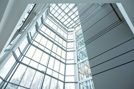 Glass wall and window of large contemporary business center or office building that is part of its interior Фото со стока