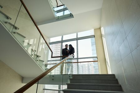 Two young colleagues in formalwear standing by railinigs between staircases inside large contemporary business center Banco de Imagens