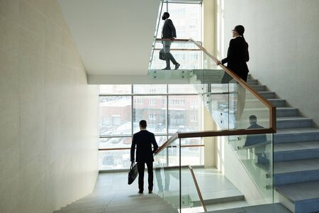 Young business people walking upstairs for work and elegant office manager moving downstairs while going home Stock Photo