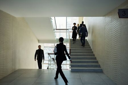 Several young intercultural people in formalwear moving upstairs and forward inside large contemporary business center