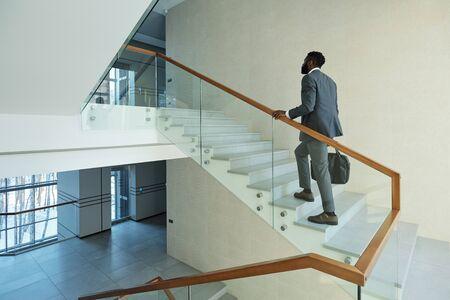 Junger eleganter afrikanischer Geschäftsmann mit schwarzer Lederhandtasche, der nach oben zu seinem Büro im Geschäftszentrum geht