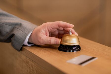 Hand of traveling businessman pushing ring button on wooden reception counter