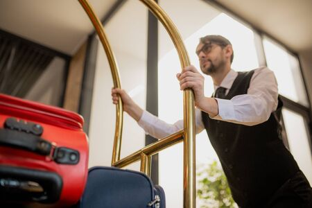 Contemporary porter holding by handles while pushing cart with suitcases 스톡 콘텐츠