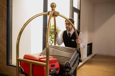 Elegant porter in eyeglasses pushing cart with pile of suitcases inside hotel 스톡 콘텐츠