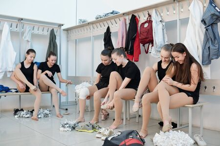 Chicas porristas descansando en el vestuario Foto de archivo