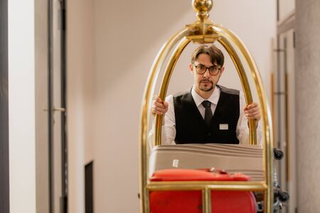 Young elegant porter in eyeglasses pushing cart with luggage of hotel guests 스톡 콘텐츠