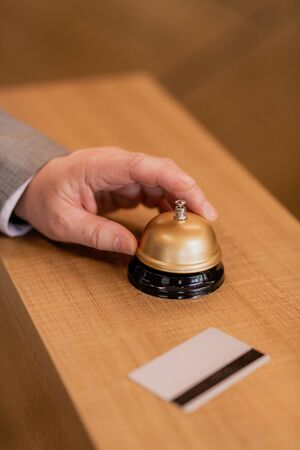 Hand of contemporary businessman over ring button on wooden reception counter