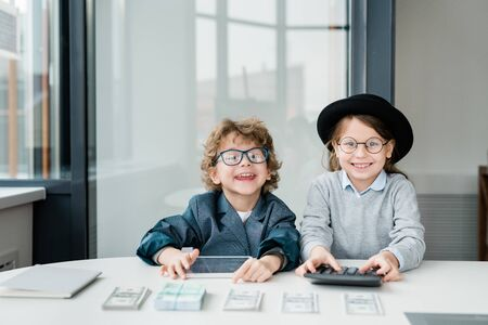 Two happy little accountants with tablet and calculator counting money