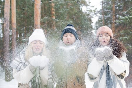 Group of young friends in winterwear blowing snow off their hands in park