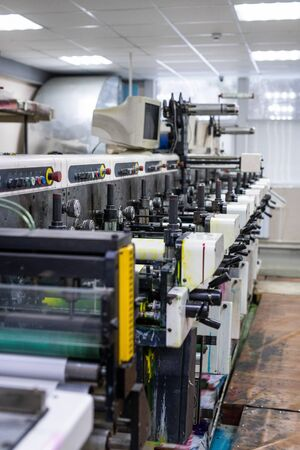 Side view of powerful printing press with computer monitor in factory shop