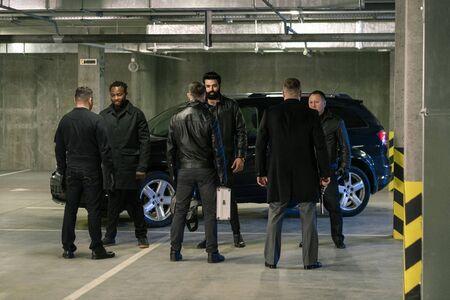 Several intercultural men in black discussing terms of criminal business