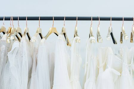 Various white dresses on hangers hanging in row on rack in wedding gown store