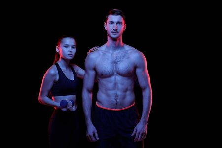 Young fit sportswoman with dumbbell standing by shirtless muscular man Imagens