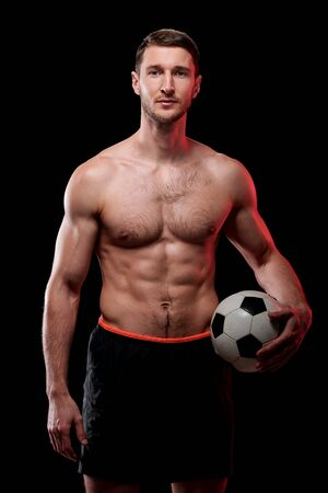 Young muscular shirtless soccer player with ball standing in front of camera