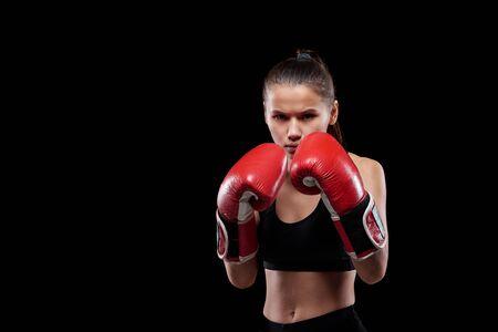 Junge ernsthafte und kraftvolle Frau in Activewear und Boxhandschuhen, die dich anschaut