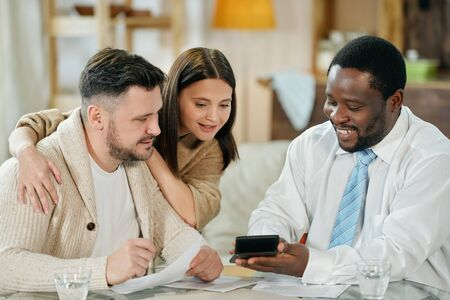 Content man advising young couple on home loan
