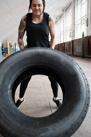Femme athlétique déterminée avec des bras tatoués renversant un gros pneu lourd