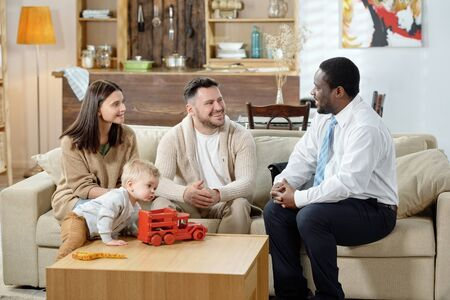 Diverse man and happy family with boy having real estate consultation sitting together on sofa