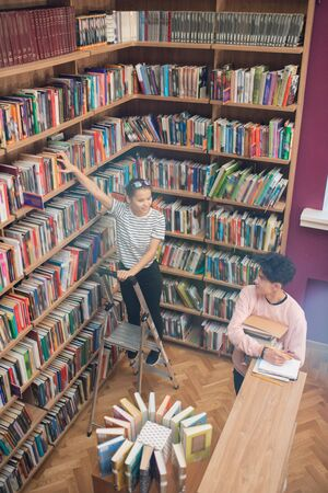 Casual teenage girl standing on stepladder by bookshelf in college library Foto de archivo
