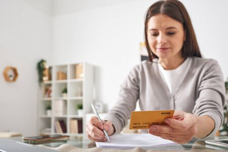 Young brunette female with credit card sitting by table and writing down or checking expenses in copybook