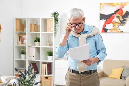 Old male pensioner in eyeglasses and casualwear looking through papers or financial documents in home environment