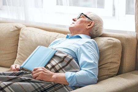 Tired senior man covered with plaid napping on couch with open book that he did not finishand fell asleep while staying at home Stock fotó