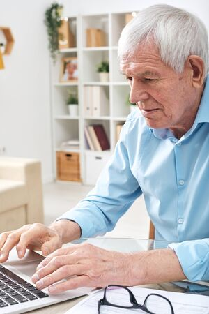 Aged retired man pressing keys of laptop keypad while surfing in the net
