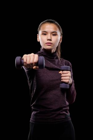 Young active female with dumbbells stretching arm forwards while exercising against black background in isolation