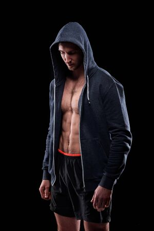 Young athlete in shorts and unzipped hoodie standing in front of camera in isolation over black background