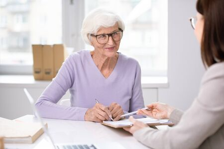 Banking specialist asking senior lady in glasses to sign document for issuance of social card