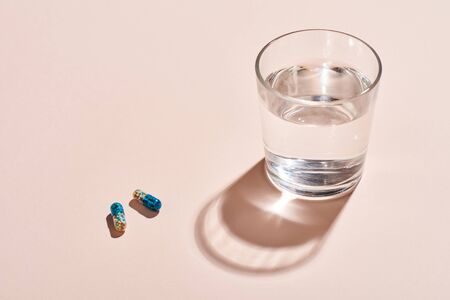 Two capsule pills and glass with water on pale pink surface horizontal shot Zdjęcie Seryjne