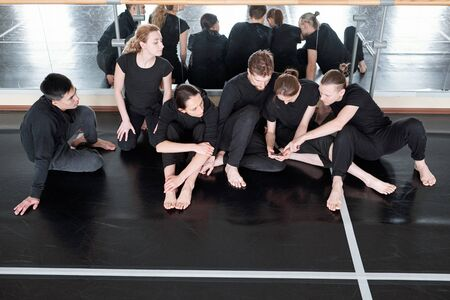 Contemporary dance teammates sitting together on floor against mirrors discussing something during break, high angle shot Stock Photo